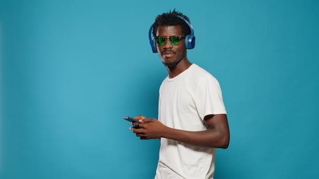 Verspielter erwachsener, der im studio zu songrhythmen über kopfhörer tanzt