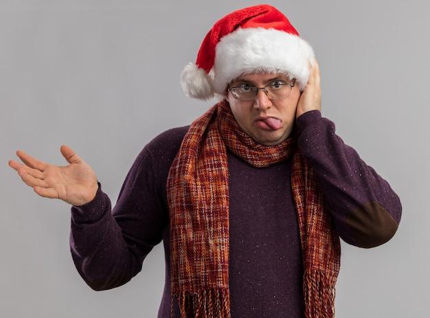 Verspielter erwachsener mann mit brille und weihnachtsmütze mit schal um den hals, der die hand auf dem kopf hält und zunge und leere hand isoliert auf weißer wand zeigt