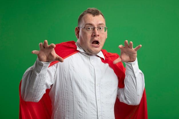 Verspielter erwachsener slawischer superheldenmann im roten umhang, der die brille trägt, die kamera tut, die tigergebrüll und pfotengeste tut, lokalisiert auf grünem hintergrund