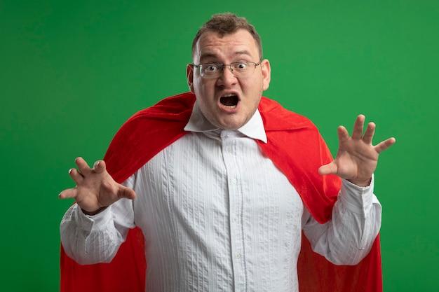 Verspielter erwachsener slawischer superheldenmann im roten umhang, der eine brille trägt, die tigergebrüll und pfotengeste tut, die auf grüner wand lokalisiert werden