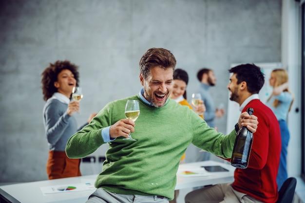 Verspielter geschäftsmann, der ein glas champagner und eine flasche tanzt und hält. im hintergrund sind seine kollegen, die trinken und erfolge feiern. boardroom-interieur.