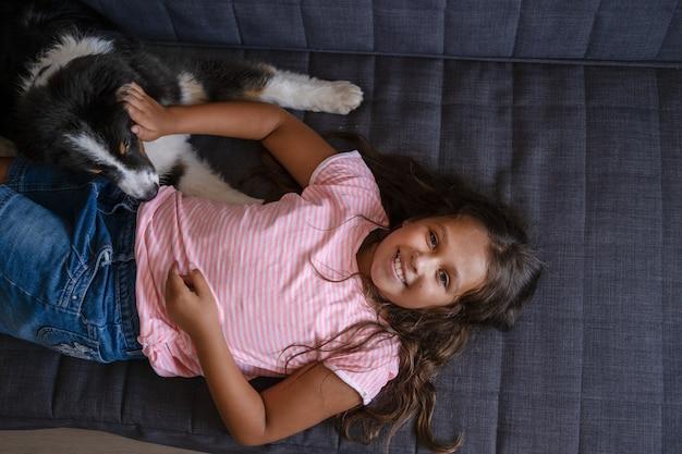 Verspielter glücklicher australian shepherd drei farben hündchen liegend spielen mit dem besitzer attraktives kaukasisches mädchen im grundschulalter.