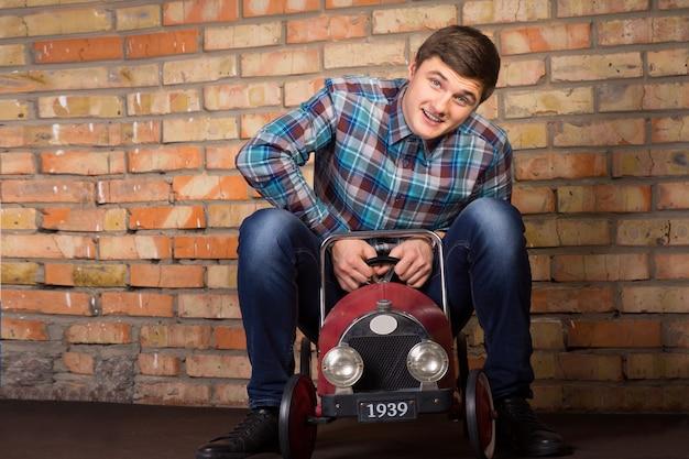 Verspielter, gutaussehender junger mann, der spaß hat, einen vintage-spielzeugwagen vor einer wand zu fahren und mit einem glücklichen lächeln in die kamera schaut