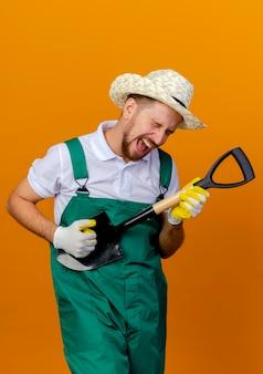 Verspielter junger hübscher slawischer gärtner in der uniform, die hut und gartenhandschuhe hält, die spaten halten, so tun, als würden sie gitarre mit geschlossenen augen spielen, die auf orange wand lokalisiert werden