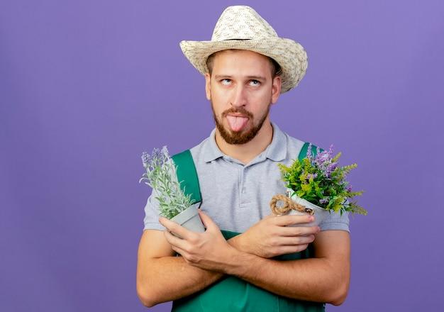 Verspielter junger hübscher slawischer gärtner in der uniform und im hut, die blumentöpfe halten, die oben zeigend die zunge lokalisiert auf lila wand mit kopienraum halten