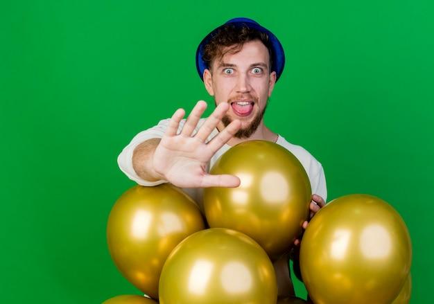 Verspielter junger hübscher slawischer party-typ, der partyhut trägt, der hinter luftballons steht, die kamera betrachten, die hand in richtung kamera gestikulierender stopp lokalisiert auf grünem hintergrund mit kopienraum ausdehnt