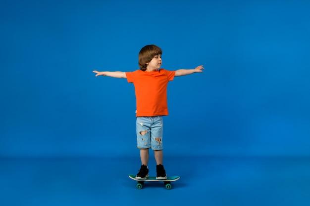 Verspielter kleiner junge mit braunen haaren reitet ein skateboard auf einer blauen oberfläche mit einem platz für text