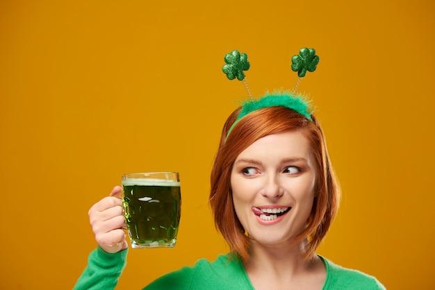 Verspielter kobold mit grünem bier
