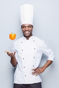 Verspielter kochmeister. selbstbewusster junger afrikanischer koch in weißer uniform, der pfeffer wirft