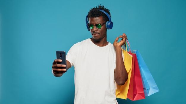 Verspielter mann, der fotos mit einkaufstüten auf dem smartphone macht