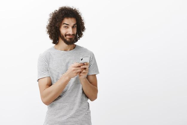 Verspielter nachdenklicher gutaussehender kerl mit lockigem haar, hält smartphone, grinst und schaut mit neugierigem fasziniertem ausdruck