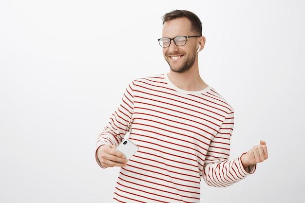 Verspielter sorgloser kaukasischer kerl mit borsten in der schwarzen trendigen brille, die augen schließt und freudig lächelt und das spielen auf unsichtbarer gitarre nachahmt