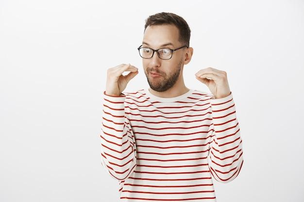 Verspielter verrückter erwachsener kerl in der schwarzen brille, im gespräch mit den händen