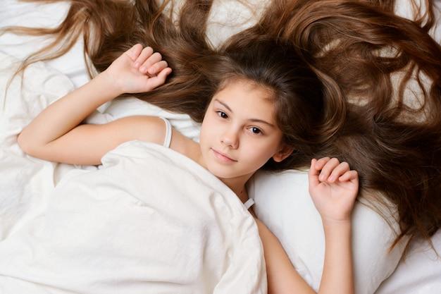 Verspieltes hübsches mädchen mit einem langen natürlichen dunklen haar liegt auf dem bett, das mit weißer weicher decke bedeckt wird. entzückendes kleines kind breitete ihr schönes haar auf dem bequemen kissen auf bett aus