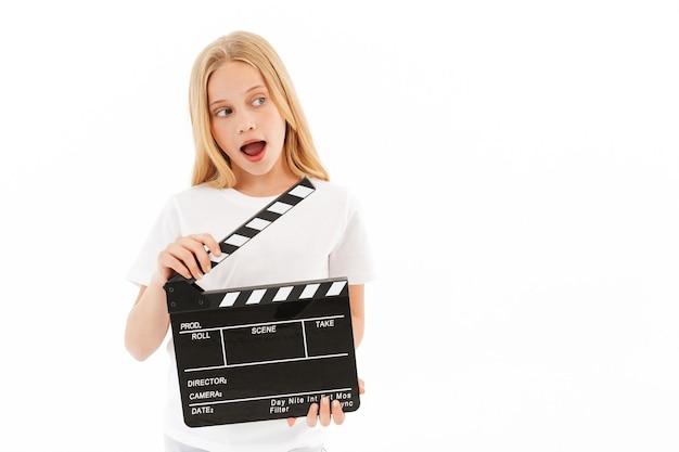 Verspieltes junges blondes mädchen in der freizeitkleidung, die filmschindel hält, während weg auf weiß schaut