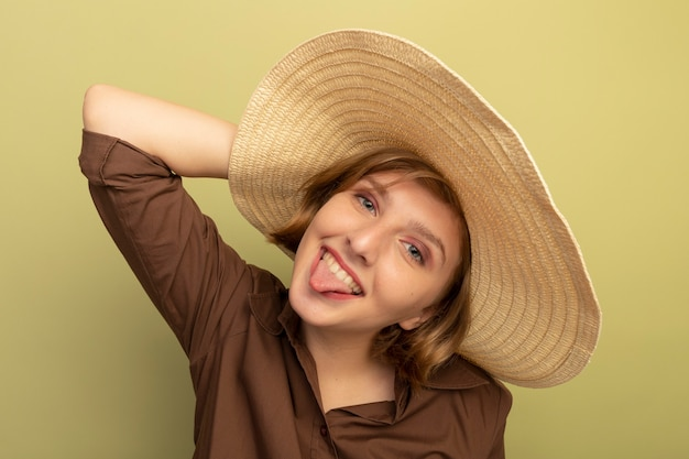 Verspieltes junges blondes mädchen mit strandhut, das den kopf berührt und zunge zeigt