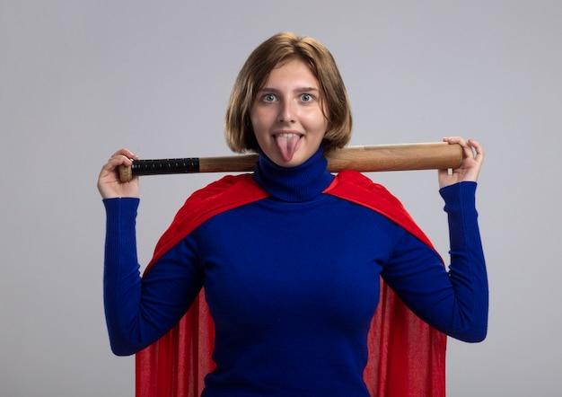 Verspieltes junges blondes superheldenmädchen im roten umhang, der baseballschläger hinter hals hält und kamera betrachtet, die zunge lokalisiert auf weißem hintergrund zeigt