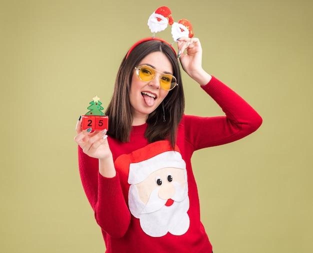 Verspieltes junges hübsches kaukasisches mädchen, das weihnachtsmann-pullover und stirnband mit brille trägt, die weihnachtsbaumspielzeug mit datum halten
