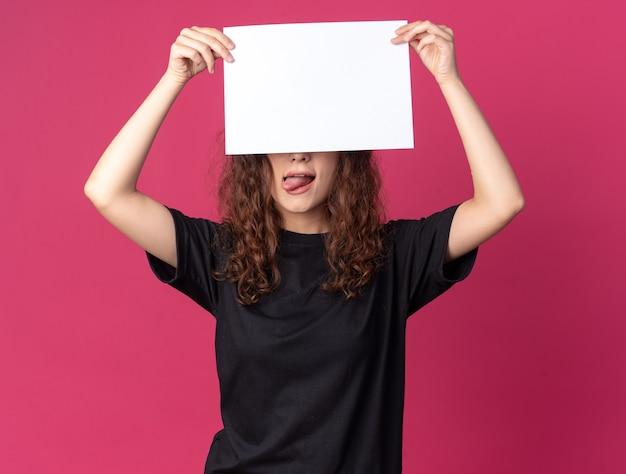 Verspieltes junges hübsches mädchen, das leeres papier anhebt, das es vor die augen hält und die zunge isoliert auf der purpurroten wand zeigt