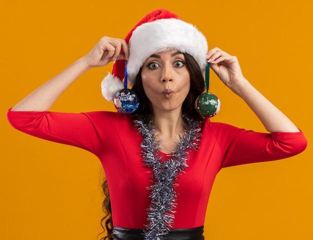 Verspieltes junges hübsches mädchen, das weihnachtsmütze und lametta-girlande um hängenden hängenden weihnachtskugeln auf ohren trägt, die kamera betrachten, die fischgesicht lokalisiert auf orangefarbenem hintergrund macht