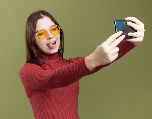 Verspieltes junges hübsches mädchen mit sonnenbrille, das die zunge zeigt, die selfie macht