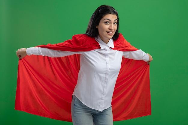 Verspieltes junges kaukasisches superheldenmädchen, das ihren heldenumhang hält und flug darstellt, der kamera lokalisiert auf grünem hintergrund betrachtet