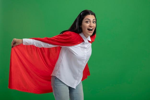 Verspieltes junges kaukasisches superheldenmädchen, das ihren heldenumhang hält und flug darstellt, der kamera lokalisiert auf grünem hintergrund mit kopienraum darstellt
