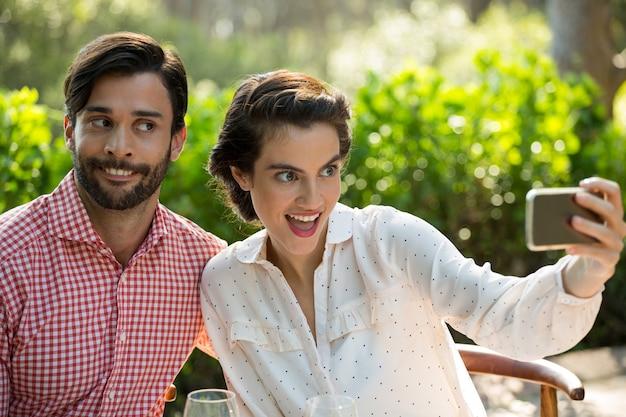 Verspieltes junges paar, das slefie durch smartphone am park nimmt