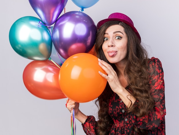 Verspieltes junges partygirl mit partyhut, das luftballons hält und die hand auf eine zeigt, die zunge isoliert auf weißer wand zeigt