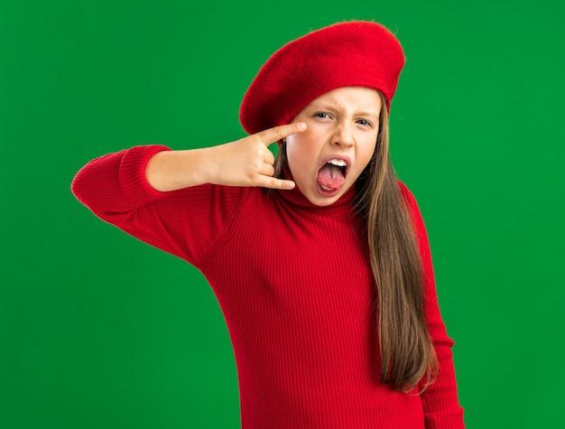 Verspieltes kleines blondes mädchen mit rotem barett, das ein felsenschild zeigt, das die zunge zeigt, die auf der vorderseite isoliert auf der grünen wand schaut