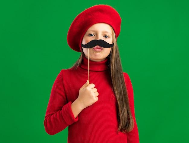 Verspieltes kleines blondes mädchen mit rotem barett, das einen gefälschten schnurrbart versucht, der auf der vorderseite isoliert auf grüner wand mit kopierraum schaut