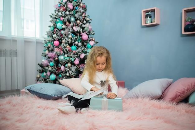 Verspieltes kleines mädchen sitzt auf dem bett und öffnet ein weihnachtsgeschenk