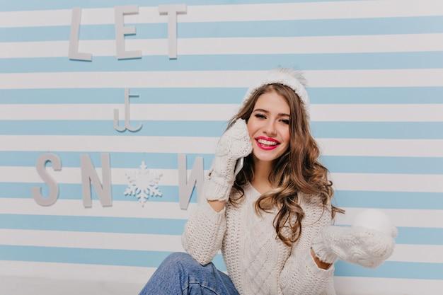 Verspieltes, kühles weibliches modell mit lächeln, schauend, schneestück in warmen fäustlingen haltend. porträt des jungen mädchens im raum mit gestreiften wänden