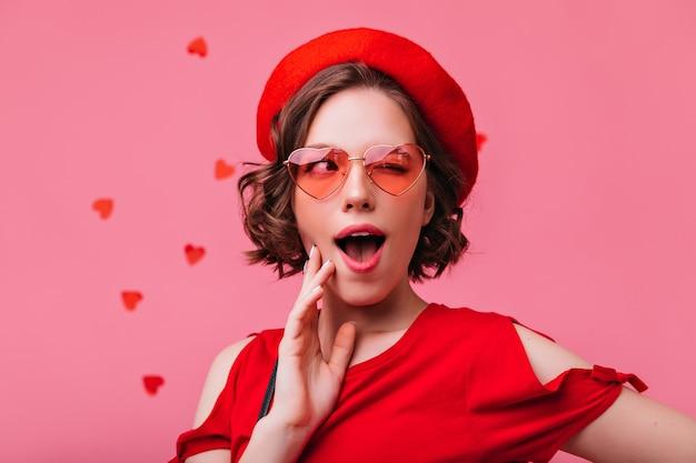 Verspieltes kurzhaariges mädchen, das während des romantischen fotoshootings steht. sinnliche französische weiße frau, die valentinstag feiert.