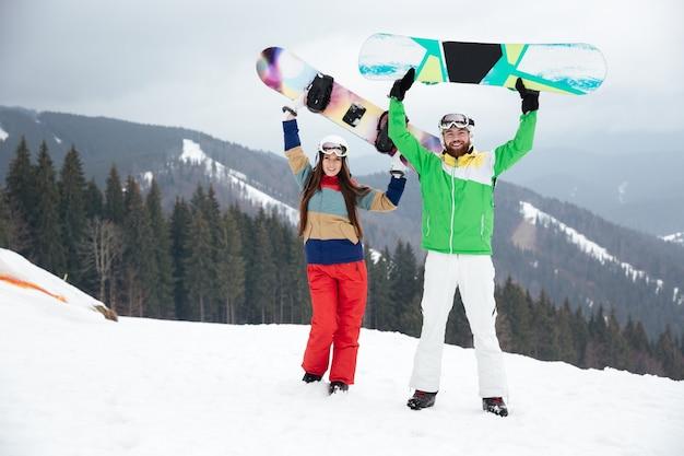 Verspieltes liebespaar snowboarder auf der piste frostiger wintertag