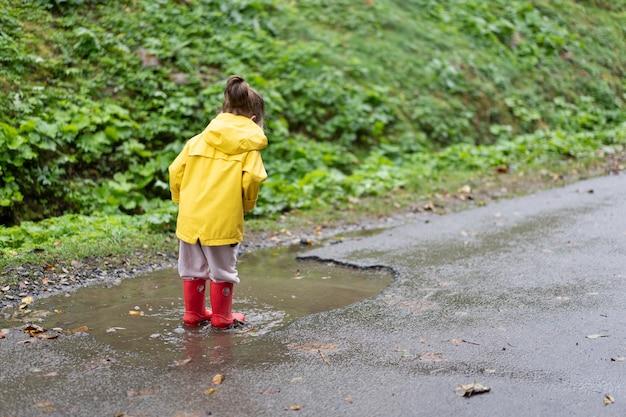 Verspieltes mädchen, das gelben regenmantel trägt, während in pfütze während des regens springt glückliche kindheit