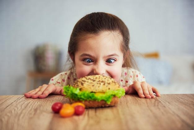 Verspieltes mädchen, das köstlichen hamburger betrachtet