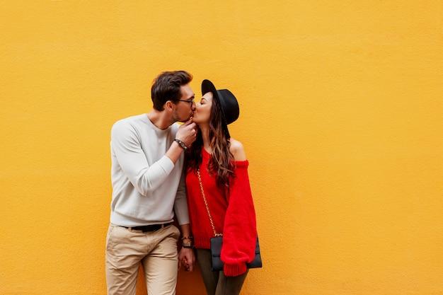 Verspieltes paar in der liebe, die über gelber wand aufwirft. reisende menschen. brünettes mädchen mit hübschem freund, der in europa reist.