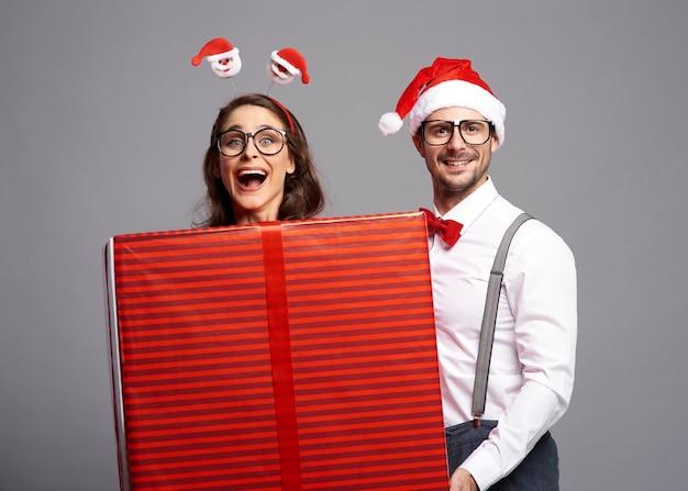 Verspieltes paar mit großem weihnachtsgeschenk