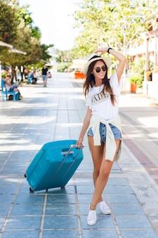 Verspieltes schlankes junges mädchen, das in einem park mit blauem koffer geht. sie trägt jeansshorts, ein weißes t-shirt, einen strohhut, eine dunkle sonnenbrille und weiße turnschuhe. sie lächelt und hat die beine gekreuzt