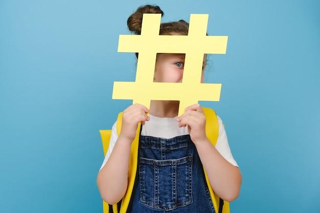 Verspieltes süßes schulmädchenkind hält gelbes papier-hashtag-zeichen, schaut lustig in die kamera, trägt rucksack und posiert einzeln auf blauer studiohintergrundwand. konzept von trendigen social-media-posts und schule