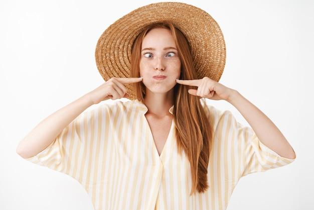 Verspieltes und freudiges gut aussehendes sorgloses ingwer-mädchen mit sommersprossen, die lustiges gesicht nachahmen, atem halten und schmollende wangen mit den fingern schmollen, um luft zu blasen, nase betrachtend