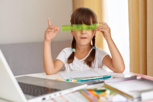 Verspieltes weibliches kind in weißem t-shirt, das am tisch vor geöffnetem notizbuch sitzt, augen mit grünem lineal bedeckt, fernunterricht während der quarantäne, finger nach oben zeigend, idee habend.