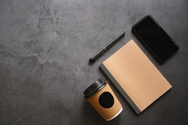 Verspotten sie den arbeitsbereich von smartphone, notebook, kaffee und stift auf einem dunklen steintisch