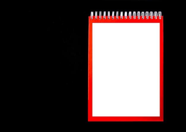 Verspotten sie den roten spiralblock auf dem schwarzen hintergrundnotizbuchplatz für text