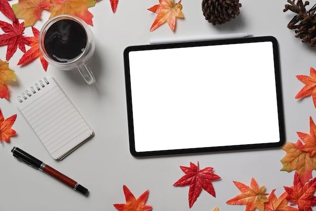 Verspotten sie digitale tablette, kaffeetasse, tannenzapfen und ahornblätter auf weißem tisch.