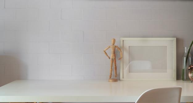 Verspotten sie herauf plakat- oder fotorahmen auf tabellenhippie-minimalismus-dachbodenschreibtischraum, kopienraum