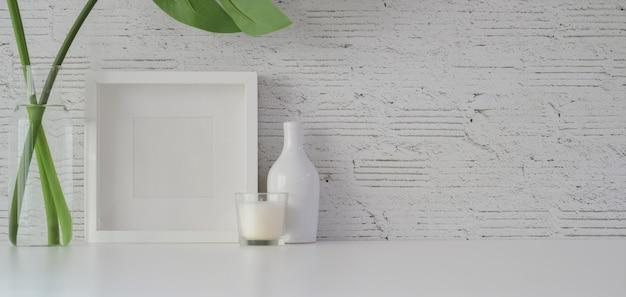 Verspotten sie herauf rahmen mit dekorationen im minimalen büroraum auf weißer tabelle und weißer backsteinmauer
