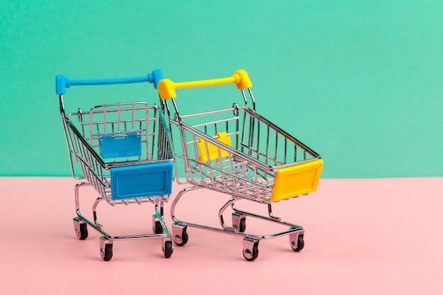 Verspotten sie herauf shoppong on-line-warenkorb auf weicher blauer wand des schreibtischtabellen-büros