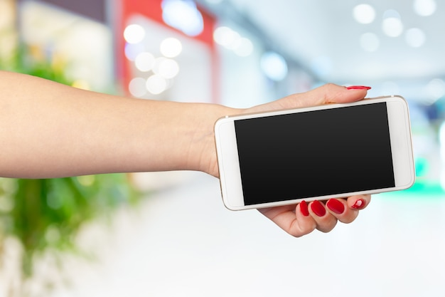 Verspotten sie herauf smartphone mit leerem bildschirm in den frauenhänden
